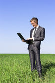 Successful, confident businessman on green field with a laptop — Stock Photo