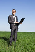 Successful, confident businessman on a green field with a laptop — Stock Photo