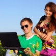 Stock Photo: Beautiful young couple in a field with a computer