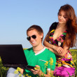 Casual happy couple on a laptop computer outdoors — Stock Photo