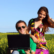 Beautiful young couple in a field with a computer — Stock Photo #9111724