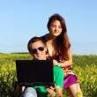 Beautiful young couple in a field with a computer — Stock Photo