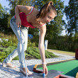 attraente giovane donna mettendo la pallina da golf sul green con foresta in — Foto Stock