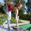 Attractive young woman putting golf ball on green with forest in — Stockfoto