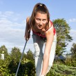 Attractive young woman putting golf ball on green with forest in — Stock Photo