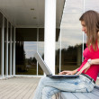 Young brunette on a bench with laptop — Stock Photo
