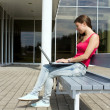 Royalty-Free Stock Photo: Young pretty woman with laptop sitting on the bench in a park