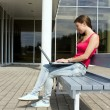 Stock Photo: Young pretty womwith laptop sitting on bench in park