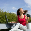 Young casual woman working on laptop outdoors — Stock Photo