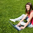 Cute teen girl sitting down on the grass studying with her lapto — Stock Photo
