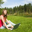 Young woman typing on a laptop outside on the grass — Stock Photo