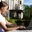 Young pretty woman with laptop sitting on the bench in a park — Stock Photo #9118440