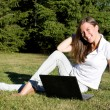 Royalty-Free Stock Photo: Smiling girl with a laptop on a lawn