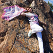 Foto Stock: Positive young girl against the rock in summer