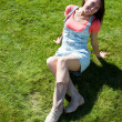 Cute brunette on the green grass in summer — Stock Photo