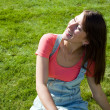 Photo: Beautiful healthy Young Woman lying on the green grass
