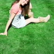 Happy young brunette on the green grass — Stock fotografie