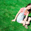 Cute brunette on the green grass in summer — Stockfoto