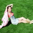 Happy young brunette with a handkerchief resting on the lawn in — Stock Photo #9118690