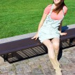 Young attractive girl model sitting on a wooden bench waiting fo — Stockfoto