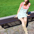 Young attractive girl model sitting on a wooden bench waiting fo — Stok fotoğraf
