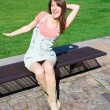 Young Woman Relaxing On A Park Bench On Clear Summers Day — Stockfoto