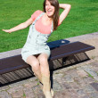 Young Woman Relaxing On A Park Bench On Clear Summers Day — Foto de Stock