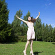 Foto Stock: Beautiful young happy woman under blue sky.