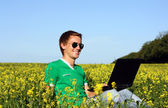 Young guy with a laptop sitting in a field — Stock Photo