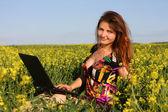 Belle brune dans une prairie jaune avec ordinateur portable — Photo