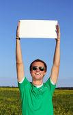 Schöne student hält ein leeres formular auf der straße — Stockfoto