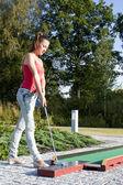 Jeune femme jouant au golf dans un club de pays — Photo