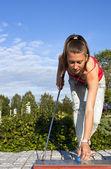 Chica joven y bella juega al golf en un día soleado, verano — Foto de Stock