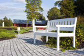 White Park bench with white fence — Stock Photo