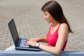 Young businesswoman working on laptop outdoor — Stockfoto