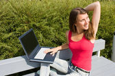 Beautiful brunette works with a laptop in the park — Stock Photo