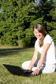 Smiling girl with a laptop on a lawn — Stock Photo