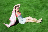 Happy young brunette with a handkerchief resting on the lawn in — Stock Photo