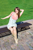 Young Woman Relaxing On A Park Bench On Clear Summers Day — Stock Photo