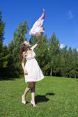 Beautiful young woman dancing with kerchief against the blue sky — Stock Photo