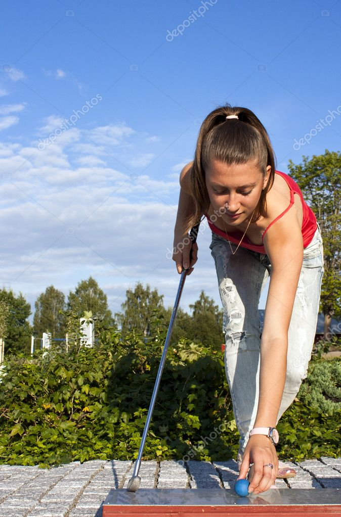 Attractive young woman putting golf ball on green with forest in the background. — Stock Photo #9117958