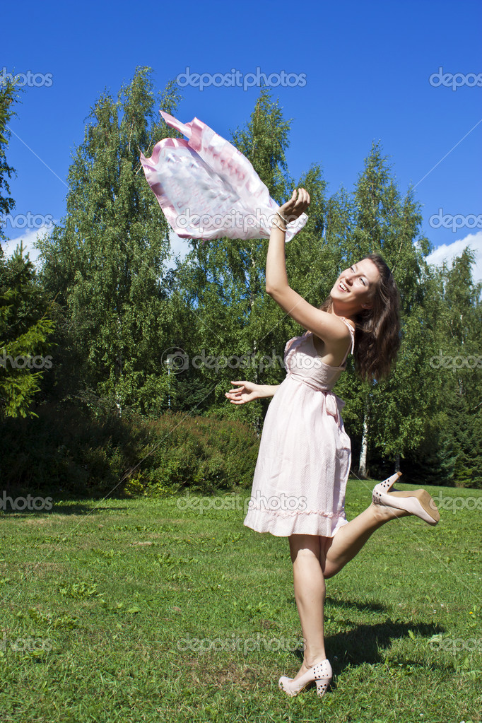Beautiful young woman dancing with kerchief against the blue sky — Zdjęcie stockowe #9119013