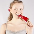 Beautiful woman teeth eating red hot chili pepper — Stock Photo