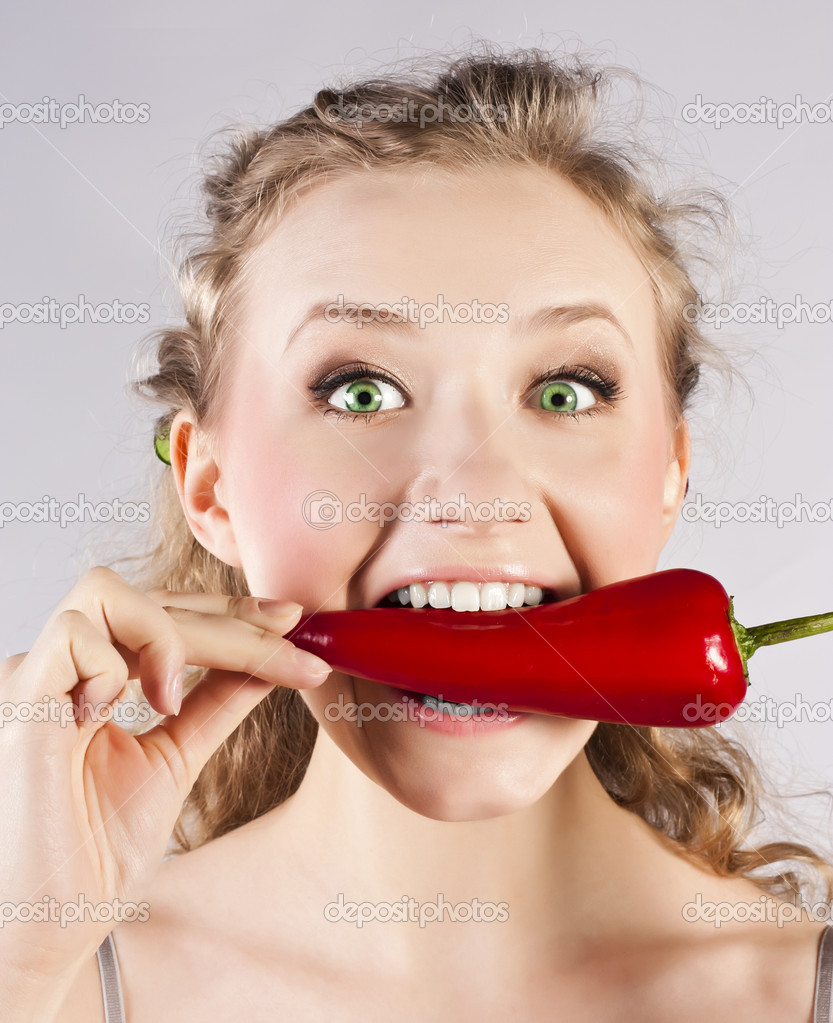 Portrait of a happy young woman holding red hot chilli in mouth  Stock Photo #9883547