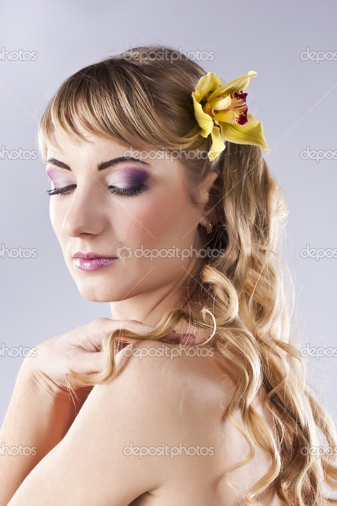 Beautiful blonde in the studio. Flower in hair — Stock Photo #9886068