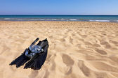 Snorkeling set lying on sand at seaside — Stock Photo