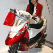 Stock Photo: Model displaying Two Wheeler at Auto Expo 2012