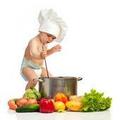 Liten pojke med slev, gryta och grönsaker — Stockfoto