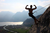 Silhouette of a rock climber flexing biceps — Stock Photo