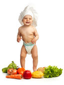 Little boy in chef's hat among fresh vegetables — 图库照片